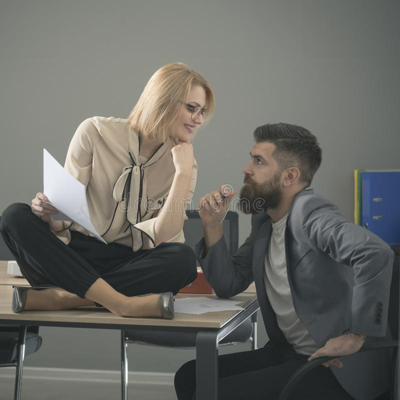 Smiling couple of young colleagues working in modern office. Two coworkers discussing work, working with documents royalty free stock images
