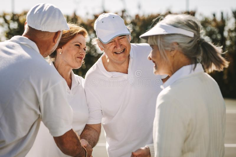 Senior men and women shaking hands after the tennis match royalty free stock photos