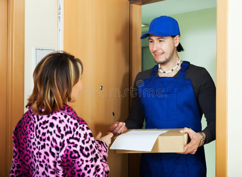 Smiling courier brought package. Smiling courier in uniform brought package to girl at home stock photography