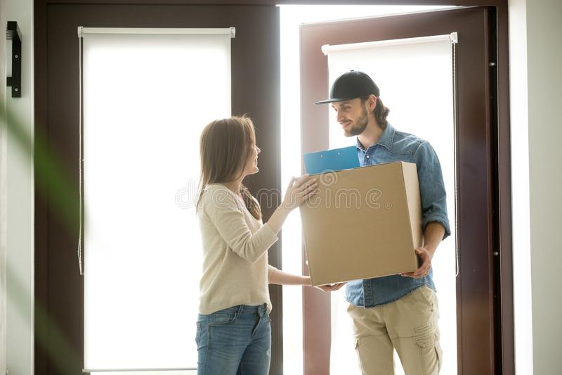 Smiling courier delivering parcel to young woman, delivery servi stock images