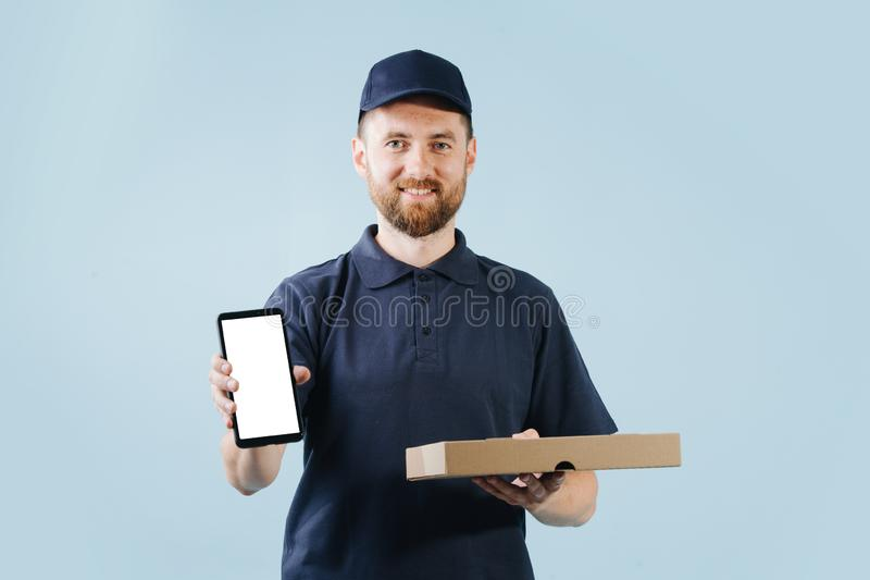 Courier is delivering pizza, holding smart phone in a hand for customer to sign. Smiling courier is delivering pizza, holding smart phone in a hand for customer royalty free stock photos