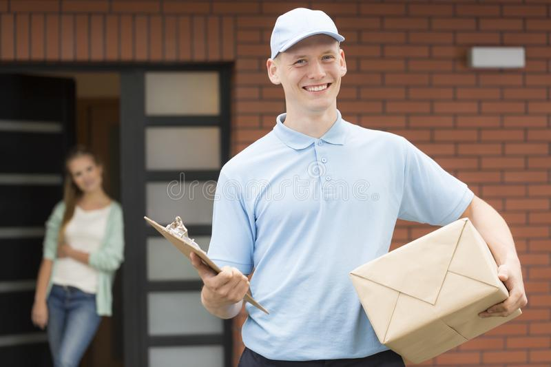 Courier in uniform holding package and delivering it to recipient. Smiling courier in uniform holding package and delivering it to recipient royalty free stock images