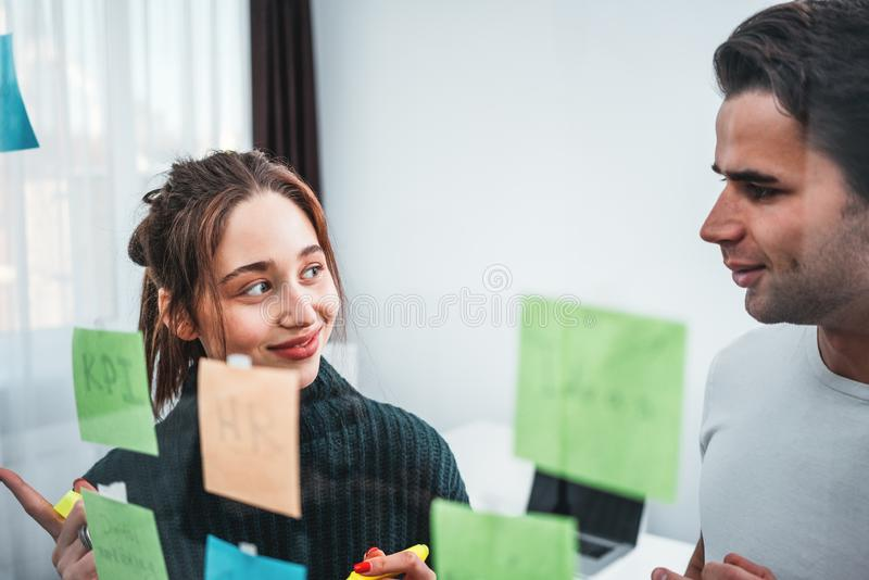 Smiling coworkers people brainstorming new business plan posted on a sticky glass note wall. Team of HR manager having meeting standing behind sticky glass royalty free stock photo