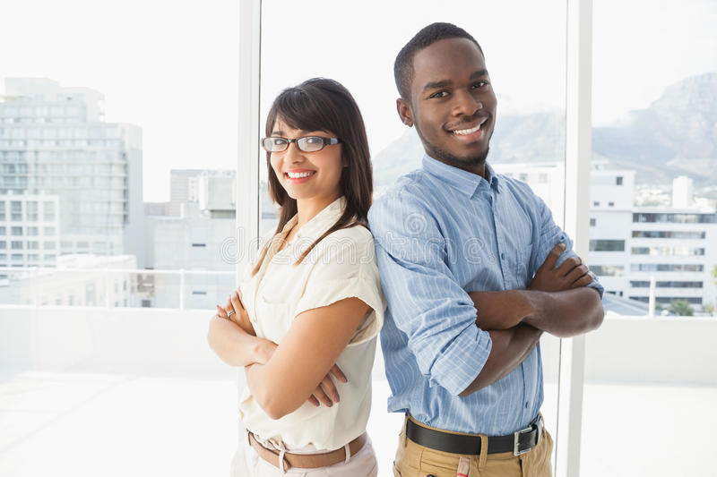 Smiling coworkers posing with arms crossed stock images