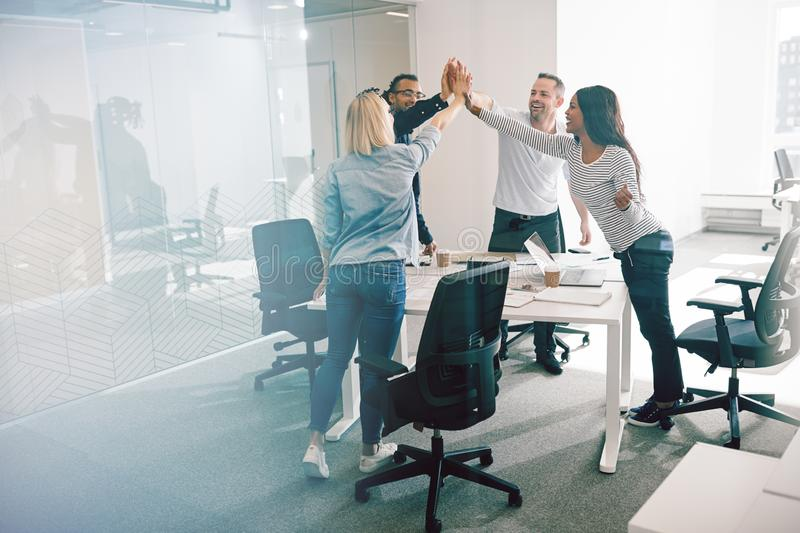 Smiling coworkers standing around an office table high fiving to stock images