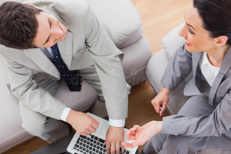 Download Smiling Coworkers Talking And Using Laptop Sitting On Sofa Stock Image - Image: 32515067