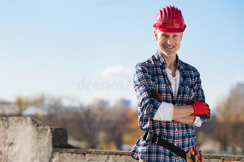 Happy proud craftsman. Smiling craftsman standing with arms folded and looking at camera. Happy construction worker with tool kit on waist and work gloves stock image