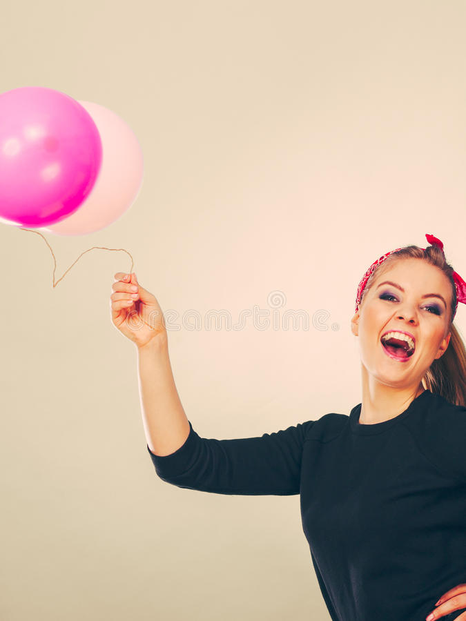Smiling crazy girl having fun with balloons. Craziness and lots of fun. Cute crazy joyful girl playing with colored balloons. Blonde playful retro style woman royalty free stock image