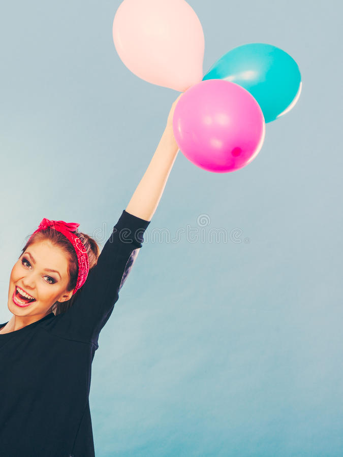 Smiling crazy girl having fun with balloons. Craziness and lots of fun. Cute crazy joyful girl playing with colored balloons. Blonde playful retro style woman royalty free stock photography