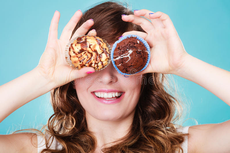 Smiling crazy woman holds cakes in hand. Bakery, sweet food and happiness concept. Closeup smiling woman having fun holding cakes in hands covering eyes with royalty free stock photography
