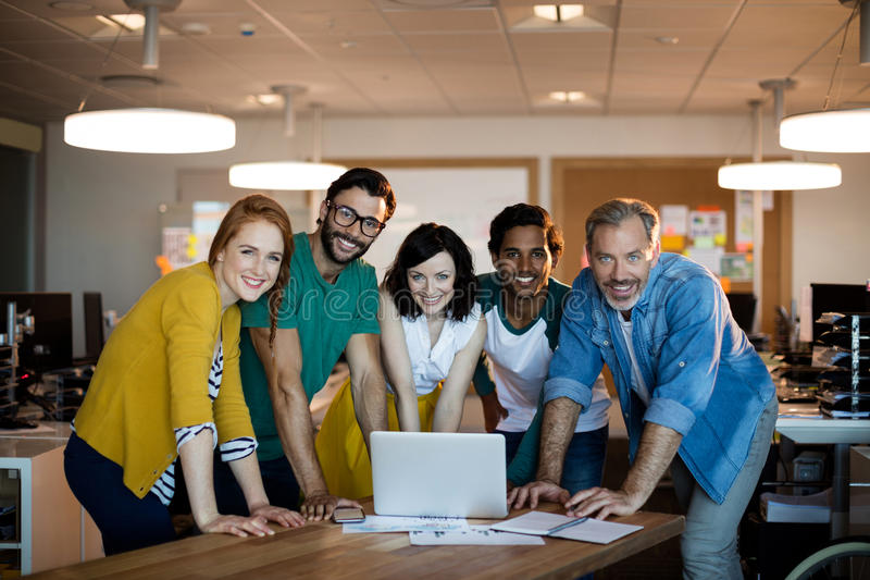 Smiling creative business team leaning on desk and using laptop in office royalty free stock images