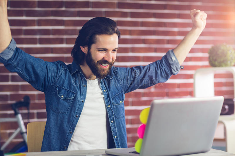Smiling creative businessman with arms raised looking at laptop royalty free stock photography