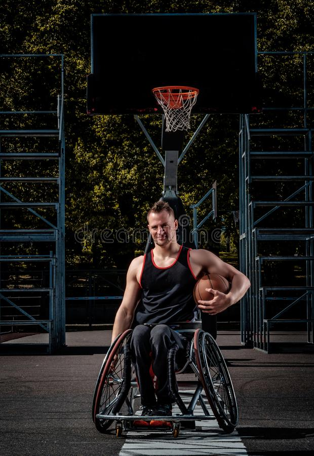 Smiling cripple basketball player in wheelchair holds a ball on open gaming ground. Smiling cripple basketball player in a wheelchair holds a ball on open royalty free stock photo