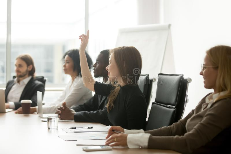 Smiling curious businesswoman raising hand at group meeting voti. Smiling curious young businesswoman raising hand at multiracial group meeting engaging in royalty free stock photography