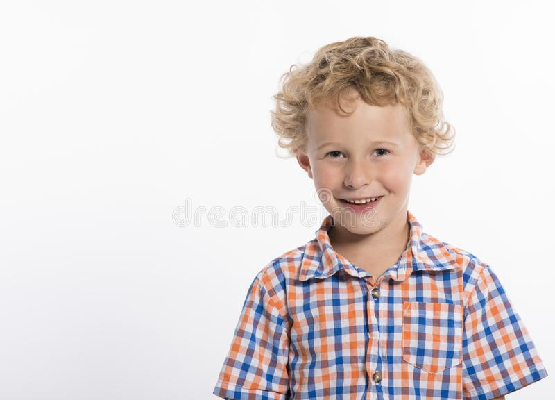 Smiling, curly haired boy isolated on white background stock photography