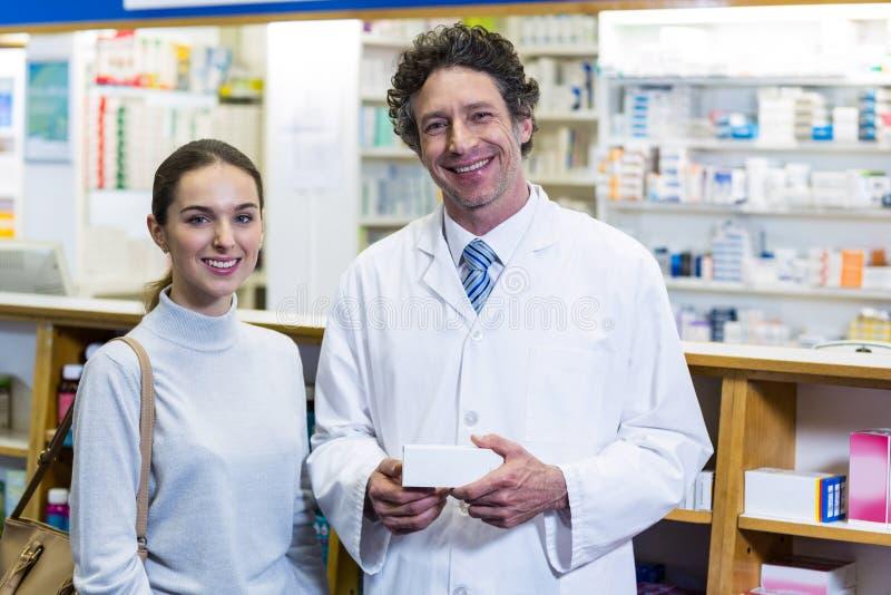Smiling customer and pharmacist holding drug box in pharmacy. Portrait of smiling customer and pharmacist holding drug box in pharmacy stock photos