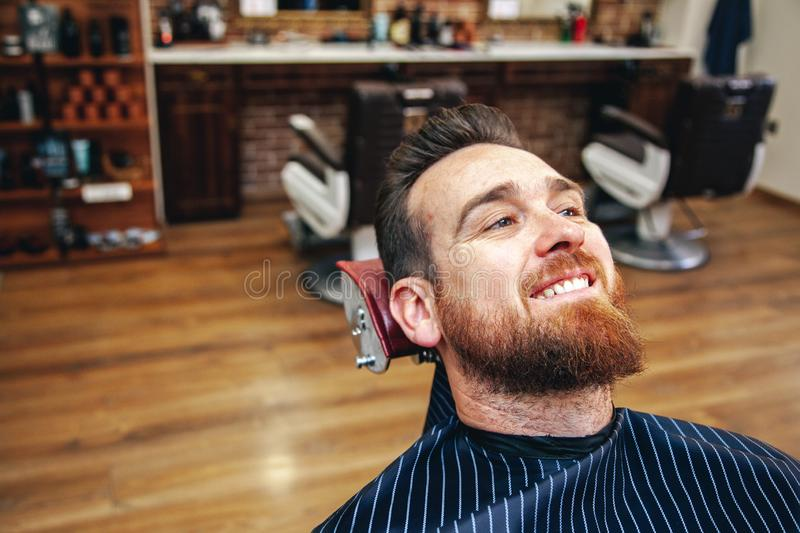 A customer waits to be seen at a barbershop stock images