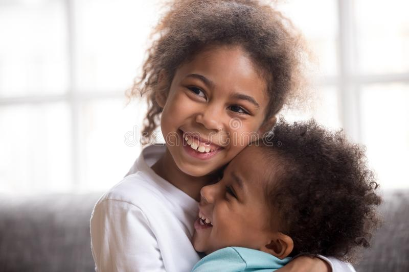 Funny black siblings hug making peace after fight. Smiling cute African American girl hug little toddler brother show love and affection, funny mixed race sister stock photos