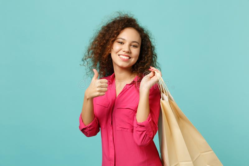 Smiling cute african girl showing thumb up, holding package bag with purchases after shopping isolated on blue turquoise royalty free stock image
