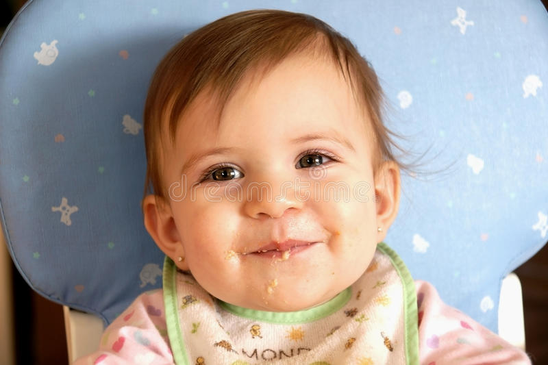Download Smiling Cute Baby Girl Eating Cereal Stock Image - Image of hair, chair: 12850257