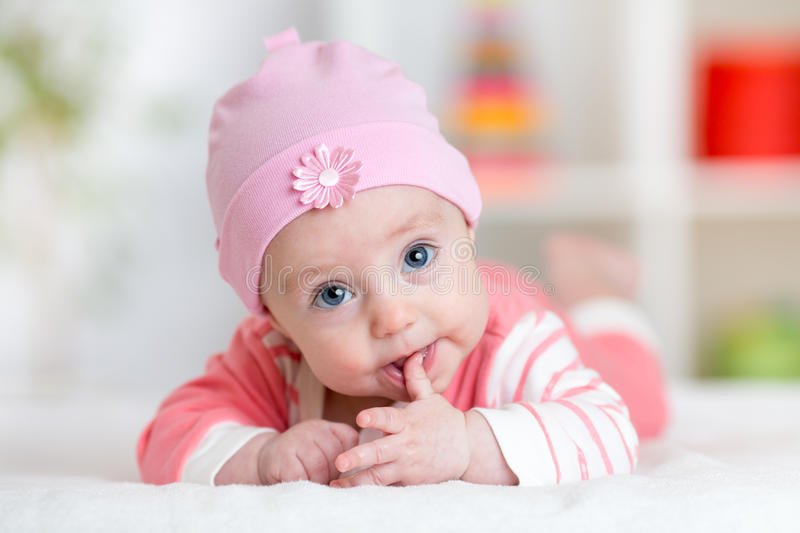 Smiling cute baby lying on her tummy in nursery room stock image
