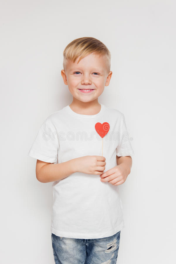 Smiling cute boy holding little paper heart in his hand against white background royalty free stock photos