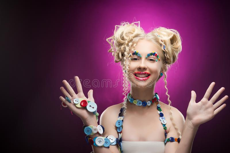 Smiling cute face nice blonde child girl wearing DIY bijou accessories made of multi-colored buttons shows her palms stock photos
