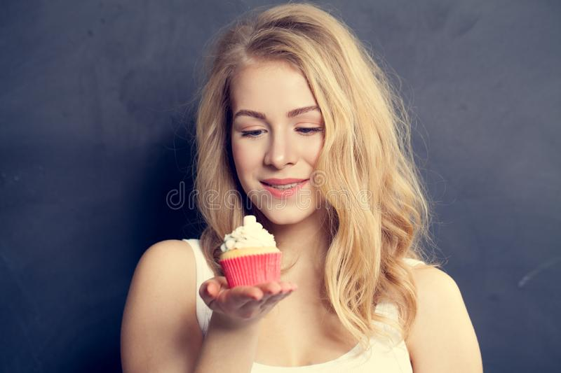 Smiling Cute Girl holding Cake in her hands. Beautiful Woman royalty free stock image