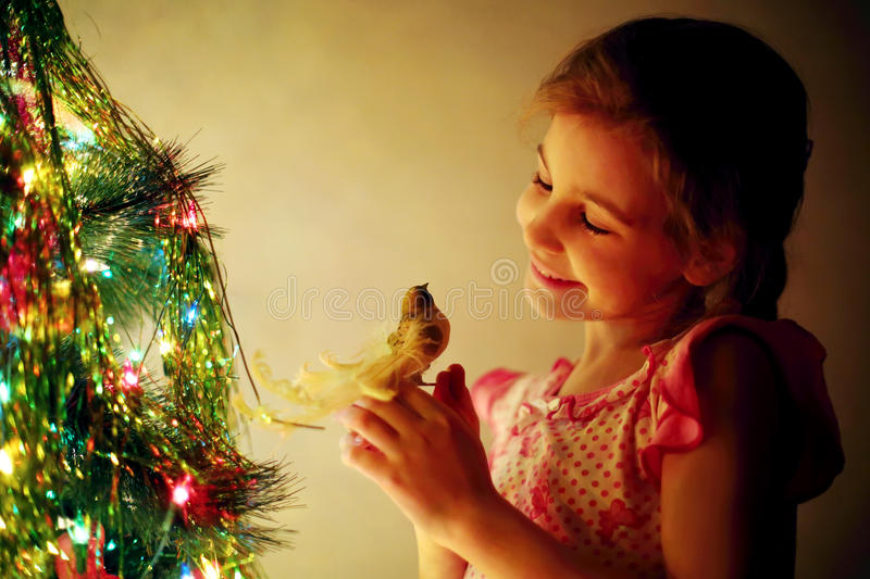 Smiling cute girl holds toy bird next to Christmas tree. At evening royalty free stock photo