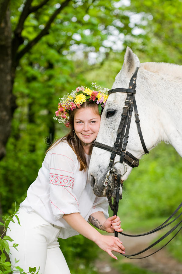 Smiling cute girl with horse. In the forest stock image