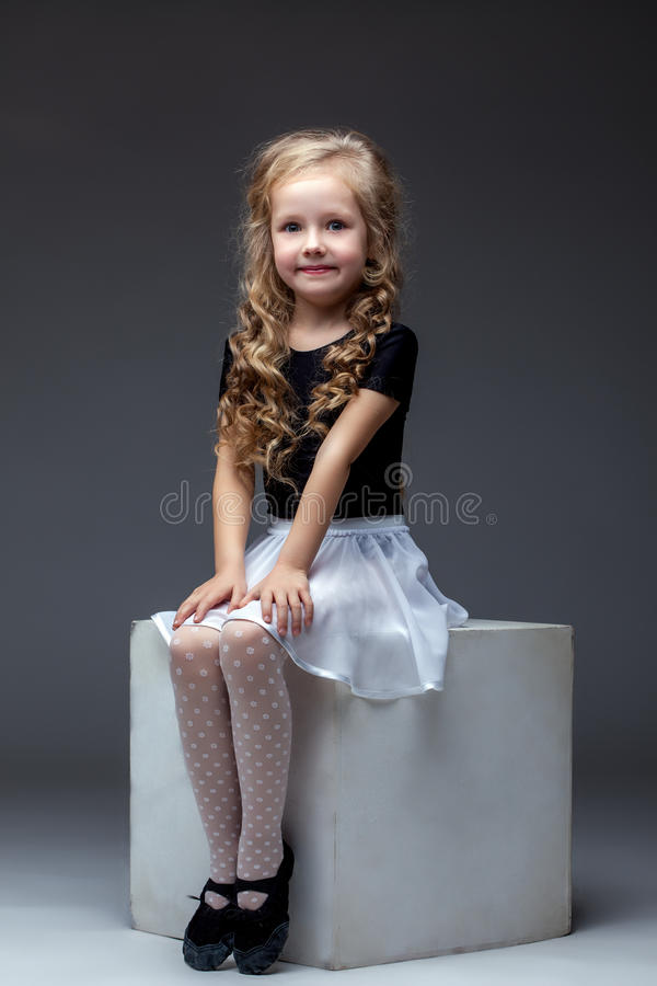 Smiling cute girl posing sitting on cube in studio royalty free stock image