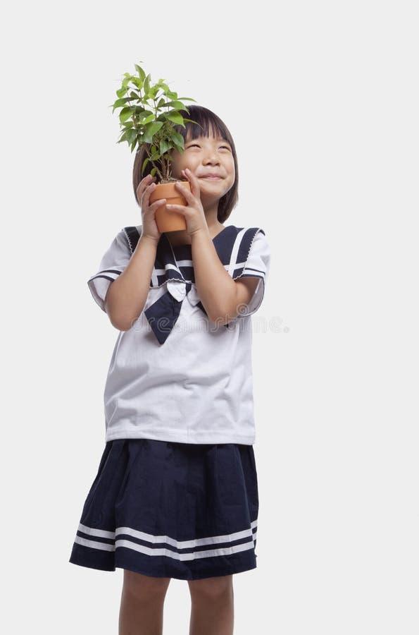 Smiling cute girl in school uniform hugging potted plant, studio shot stock photo