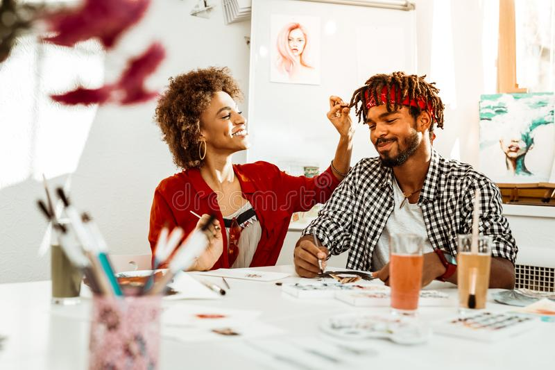 Smiling cute girlfriend touching dreadlocks of her man stock photos