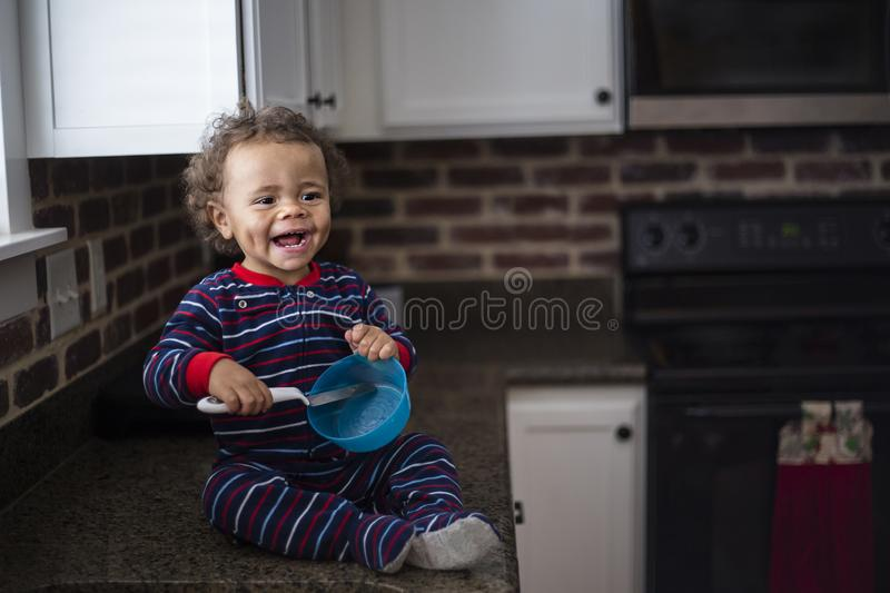 Smiling Cute little black baby boy playing in the kitchen. Having fun playing with parents and with kitchenware. Adorable expression by a mixed race child royalty free stock photos