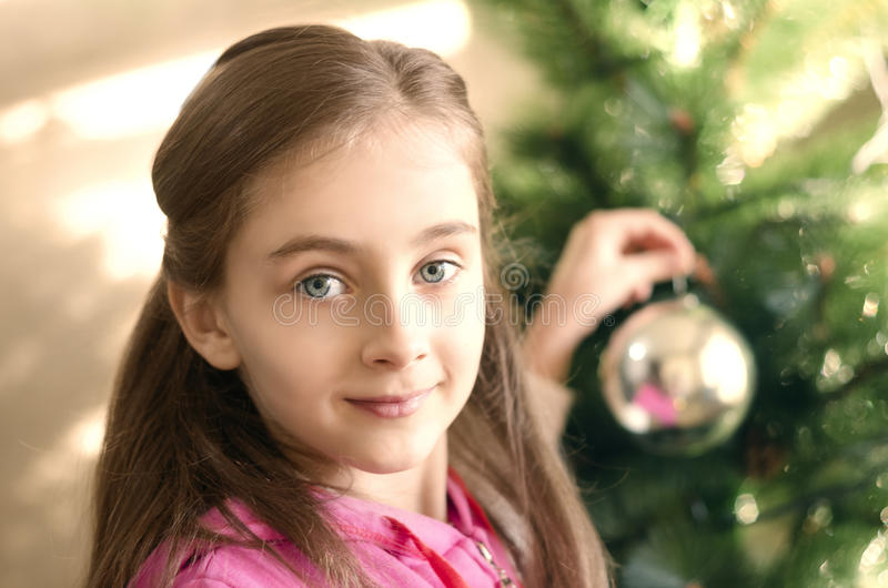 Smiling cute little child girl is decorating the Christmas tree royalty free stock photos