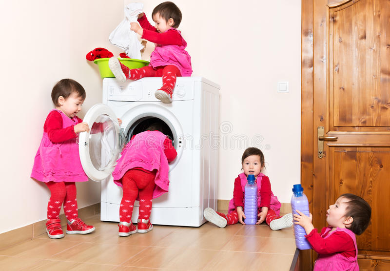 Smiling cute little child using washing machine at home stock image