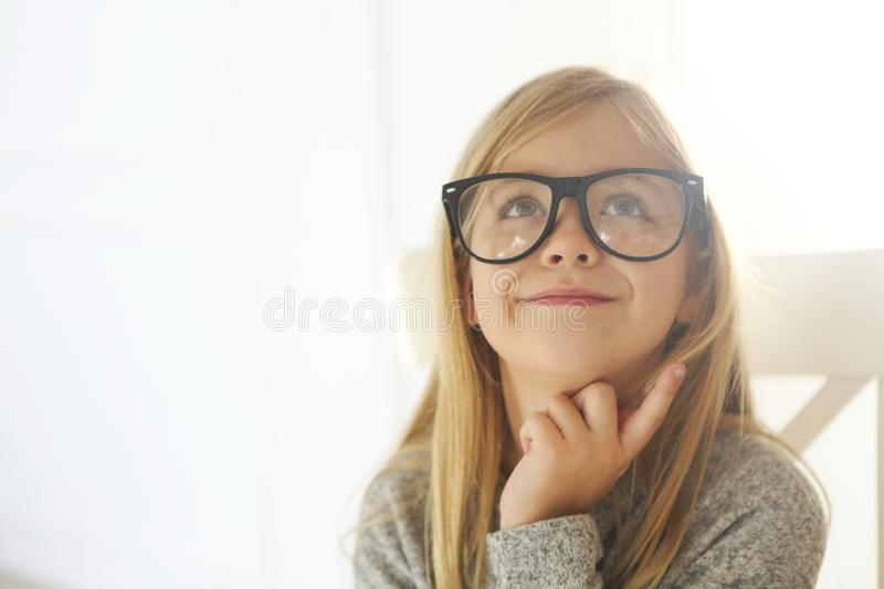 Smiling cute little girl with black eyeglasses over white background stock images
