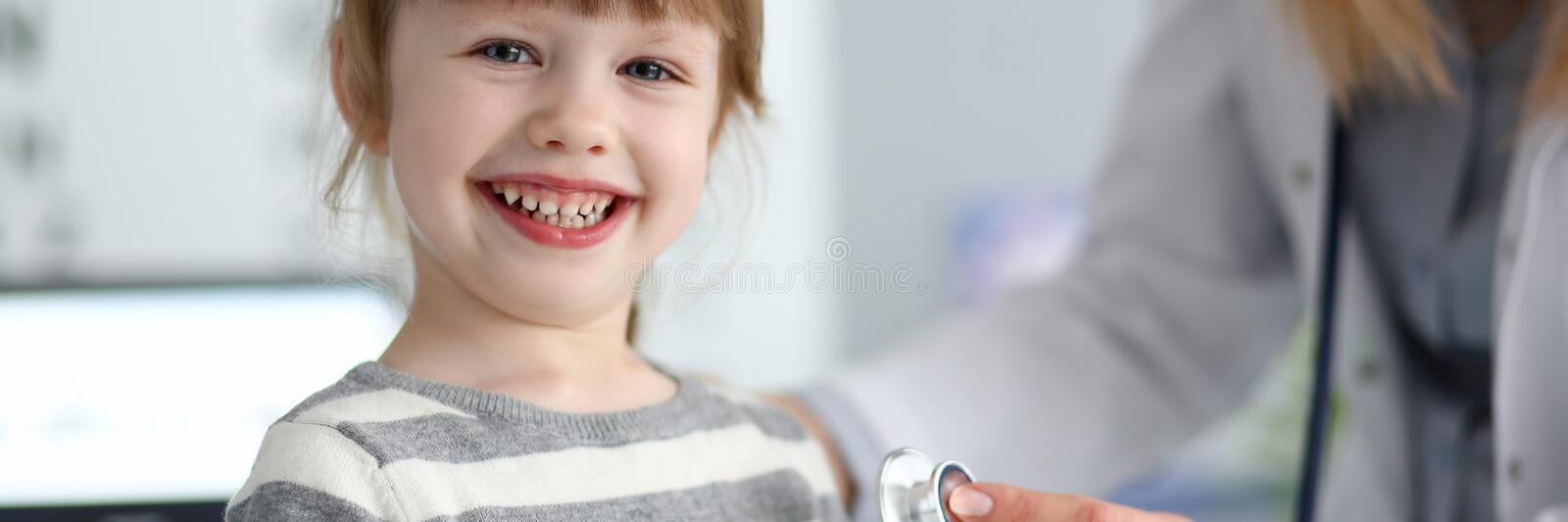 Smiling cute little girl with doctor measuring heart beat with stethoscope royalty free stock photos
