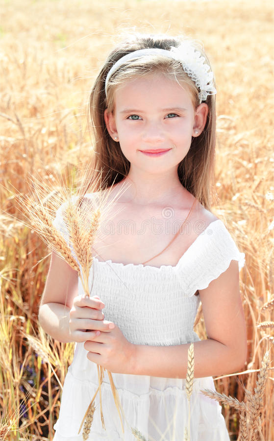 Smiling cute little girl on field of wheat stock images