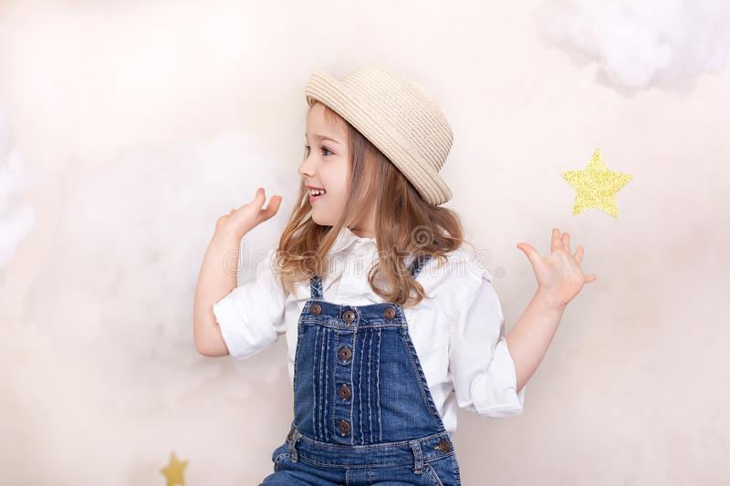 A smiling cute little girl flies in the sky with clouds and stars. Little astrologer Little traveler. The concept of preschool edu stock images