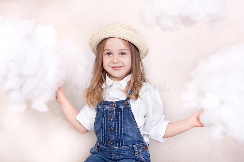 A smiling cute little girl flies in the sky with clouds and stars. Little astrologer Little traveler. The concept of preschool edu royalty free stock images