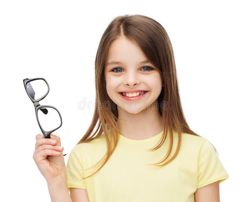 Smiling cute little girl holding black eyeglasses stock photos