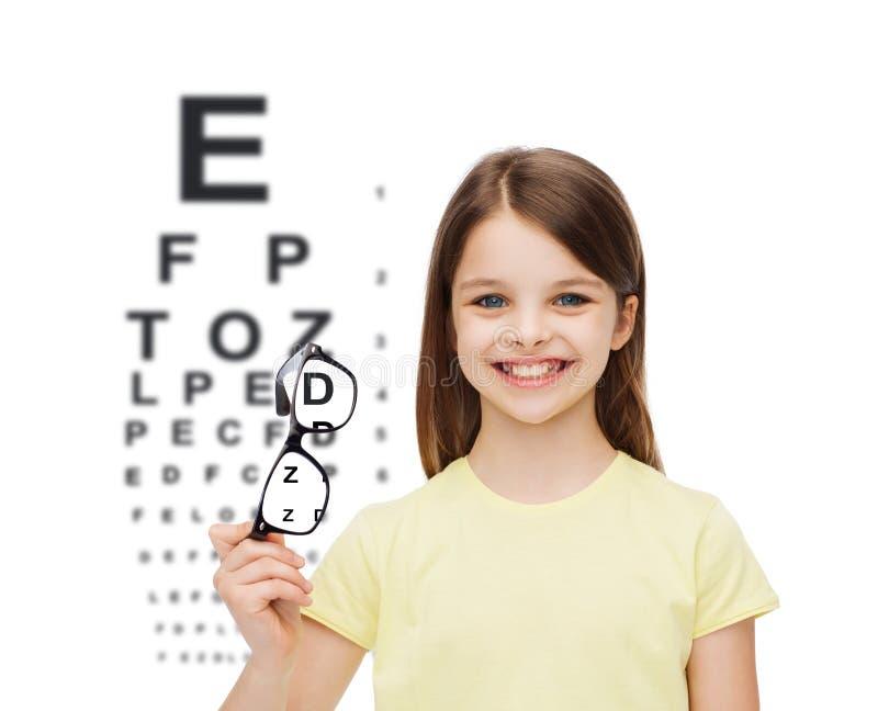 Smiling cute little girl holding black eyeglasses stock images
