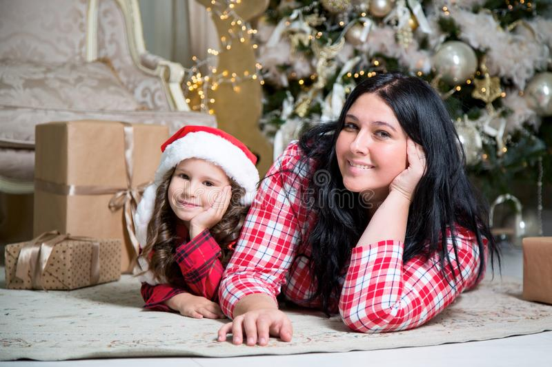 Smiling cute little girl with santa hat and mother near gifts and Christmas tree. New year or Christmas family celebration at home stock photos