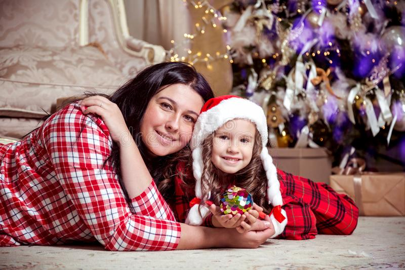 Smiling cute little girl in santa hat and mother near gifts and Christmas tree. New year or Christmas family celebration at home.  royalty free stock photography