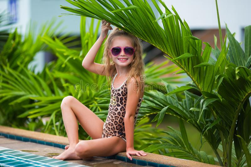 Smiling cute little girl in sunglasses in pool in sunny day royalty free stock images