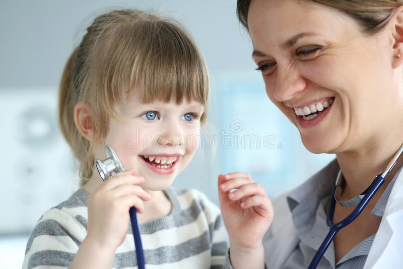 Smiling cute little patient interacting with female doctor stock image