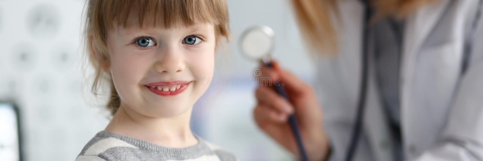 Smiling cute little patient interacting with female doctor stock photo