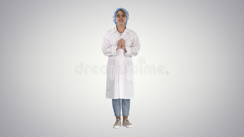 Smiling cute medical doctor woman talking to camera on gradient background. royalty free stock images