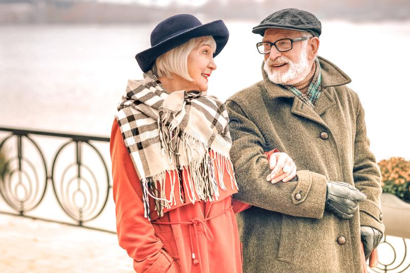 Smiling cute senior couple looking lovingly at each other stock images